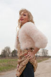 Young blond woman in a beige dress and a short pink fur coat on the countryside road Royalty Free Stock Images