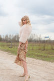 Young blond woman in a beige dress and a short pink fur coat on the countryside road Royalty Free Stock Photos
