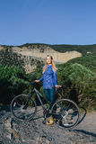 Young blond woman with the bike and enjoying life the on background mountains Stock Photos