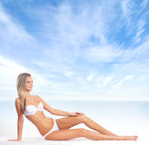 A young blond woman in bikini on the beach Royalty Free Stock Photos