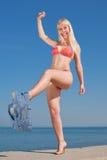 Young blond woman in bikini outdoors. Laughing blond woman in bikini undresses outdoors Stock Photos