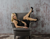 Young blond woman in a black evening dress and shoes sitting on a stool Stock Image