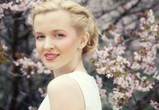 Young blond woman  in blooming sakura garden Royalty Free Stock Photography