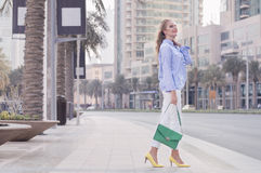 Young blond woman in blue blouse, white trousers, yellow shoes Royalty Free Stock Photography