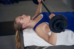 Young blond woman in blue top doing bench pressing Royalty Free Stock Photos