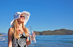 Young blond woman with bottle of water. Young smiling blond caucasian white woman with hat and sunglasses holding bottle of water. Clear blue sky, sea and island Stock Image