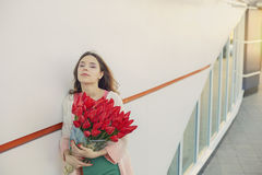 Young blond woman with a bouquet of red tulips Royalty Free Stock Photos