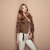 Young blond woman in brown jacket. And white jeans. Girl posing on a beige background. Jewelry and hairstyle. Fashion photo Stock Photography