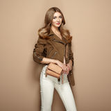 Young blond woman in brown jacket. And white jeans. Girl posing on a beige background. Jewelry and hairstyle. Girl  with  brown handbag. Fashion photo Stock Images