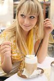 Young blond woman in a cafe with latte macchiato Royalty Free Stock Image