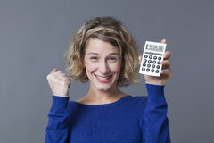 Young blond woman clenching fist and calculator Royalty Free Stock Photo
