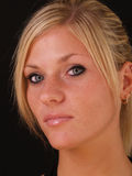 Young blond woman closeup portrait serious. Young blond woman portrait closeup black background Royalty Free Stock Photo