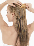 Young Blond Woman Combing Wet Hair. Rear view of a young blond woman combing her wet hair against white background Stock Images