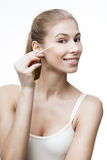 Young blond woman with cotton bud Stock Image