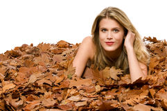 Young blond woman covered by dried leaves Stock Photos