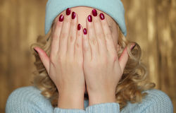 Young blond woman covering her face Royalty Free Stock Photo