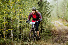 Young blond woman cyclist rides through forest Stock Photo