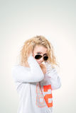Young blond woman in dark glasses and a white sweater. Beautiful young blond woman in dark glasses and a white sweater.the photo has a free space for your text Stock Image