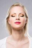 Young blond woman displaying elegant makeup. Royalty Free Stock Photography