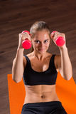 Young Blond Woman Doing Crunches with Hand Weights Stock Images