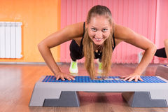Young Blond Woman Doing Push Ups in Step Class Stock Image