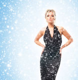 A young blond woman in a dress posing on the snow Stock Images