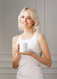 Young blond woman drinking coffee in a mug Stock Images