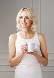 Young blond woman drinking coffee in a mug Royalty Free Stock Images