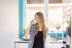 Young blond woman drinking milk from the glass. Royalty Free Stock Photography