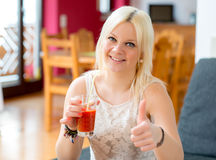 Young blond woman is drinking red juice Stock Photos