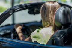 Young blond woman driving a cabriolet car stopped at a light. Stock Images