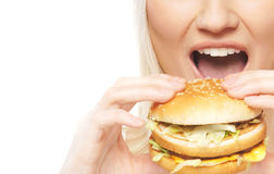 A young blond woman earing a fresh hamburger Royalty Free Stock Images