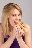 Young blond woman eating hot dog with ketchup. Beautiful blonde female biting hot dog bun with sausage and ketchup during lunch break Royalty Free Stock Photo