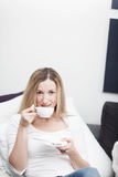 Young blond woman enjoying a cup of coffee Stock Photos