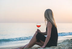 Young blond woman enjoying glass of rose wine on beach by the sea at sunset. Royalty Free Stock Photos