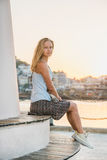 Young blond woman enjoying sunset and sitting on bench of the Alanya's Lighthouse near the water. Royalty Free Stock Images