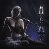 A young blond woman in erotic clothes smoking a hookah Stock Photos
