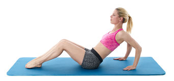 Young blond woman exercising. On a blue mat, white studio background Stock Images