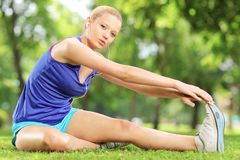 Young blond woman exercising outdoors. Young blond woman exercising outdoor in a park Stock Photos