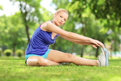 Young blond woman exercising in park. Young blond woman exercising in a park Royalty Free Stock Photos