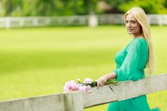 Young blond woman by the fence Royalty Free Stock Image