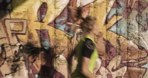 Young blond woman in fitness wear running training near grunge wall.Side following view.Summer sunny day.Industrial. Green city.Urban runner cardio healthy stock video footage