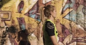 Young blond woman in fitness wear walking near grunge graffiti wall.Side following view.Summer sunny day.Industrial. Green city.Urban runner cardio healthy stock footage