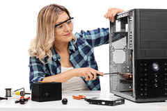 Young blond woman fixing a computer Royalty Free Stock Image
