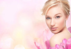 Young blond woman in flower petals. Young blond woman in flower on pink background Stock Photo