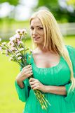 Young blond woman with flowers Stock Photos