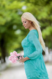 Young blond woman with flowers Stock Images