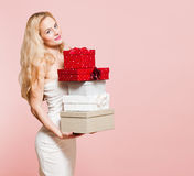 Young blond woman with gift boxes. Royalty Free Stock Photography