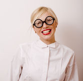 Young blond woman in glasses like bookworm Royalty Free Stock Images