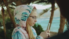 Young blond woman in glasses take picture by phone, strong wind, sea and palms on the background, slow motion, 4k